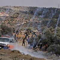 Des grenades lacrymogènes tirées par l'armée israélienne atterrissent au milieu de manifestants palestiniens lors de confrontations dans la ville de Beita, près de la ville de Naplouse en Cisjordanie, le 23 juillet 2021, après une manifestation contre l'avant-poste israélien d'Evyatar. (Crédit : JAAFAR ASHTIYEH/AFP)