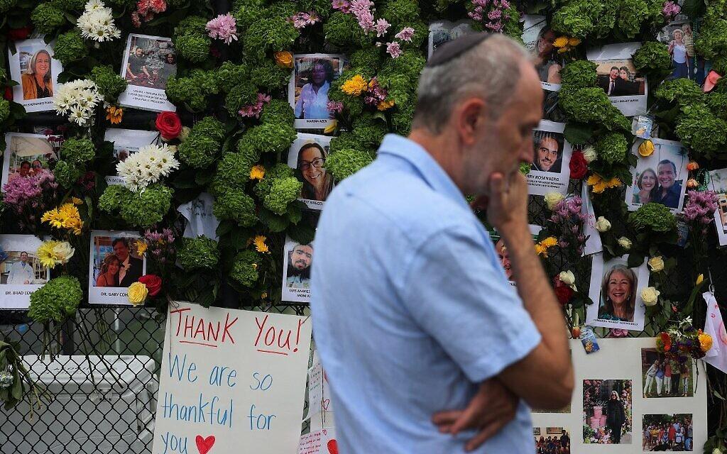 Un homme passe devant un mémorial où figurent les photos de certains des disparus de l'immeuble de 12 étages Champlain Towers South, à Surfside, en Floride, qui s'est partiellement effondré, le 28 juin 2021. (Crédit : Joe Raedle/Getty Images/AFP)