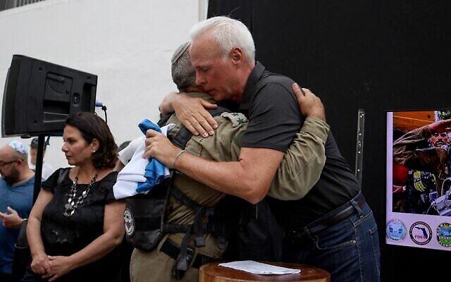 Le maire de Surfside Charles Burkett; à droite, prend dans ses bras le colonel Golan Vach,  commandant de l'unité de secours de l'armée israélienne envoyée en Floride suite à la catastrophe de Surfside, lors d'une cérémonie marquant le départ de l'équipe israélienne à  Surfside, en Floride, le 10 juillet 2021. (Crédit : Anna Moneymaker / GETTY IMAGES NORTH AMERICA / Getty Images via AFP)