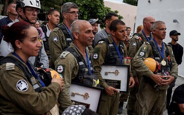 Les membres de l'équipe de secours de l'armée israélienne venue pour participer aux efforts de sauvetage qui ont suivi l'effondrement d'une tour d'habitation en Floride; avec notamment le colonel Golan Vach, deuxième à gauche, et le colonel Edri Elad, deuxième à droite, après la remise de leur distinction sous forme de clé cérémoniale à Surfside, le 10 juillet 2021. (Crédit :   Anna Moneymaker/Getty Images/AFP)