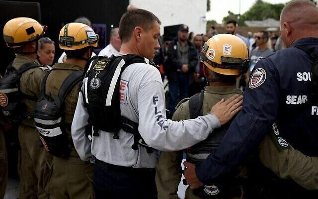SURFSIDE, FLORIDA - JULY 10: Un membre des services des sapeurs-pompiers passe le bras autour de Golan Vach, commandant de l'équipe de secours de l'armée israélienne venue pour participer aux efforts de sauvetage qui ont suivi l'effondrement d'une tour d'habitation en Floride, pendant une cérémonie à Surfside, en Floride, le 10 juillet 2021. (Crédit : Anna Moneymaker/Getty Images/AFP)