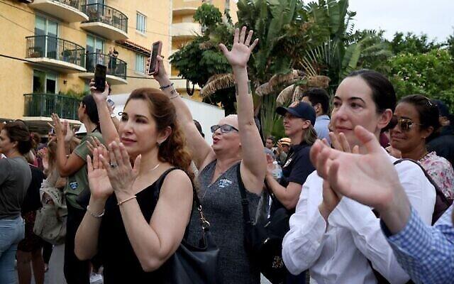 SURFSIDE, FLORIDA - JULY 10: Des Américains applaudissent  l'équipe de secours de l'armée israélienne venue pour participer aux efforts de sauvetage qui ont suivi l'effondrement d'une tour d'habitation en Floride à Surfside, le 10 juillet 2021. (Crédit :   Anna Moneymaker/Getty Images/AFP)
