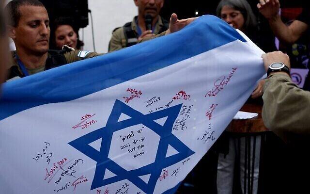 SURFSIDE, FLORIDA - JULY 10: Le drapeau israélien signé par les membres de l'équipe de secours de l'armée israélienne venue pour participer aux efforts de sauvetage qui ont suivi l'effondrement d'une tour d'habitation en Floride et remis aux autorités de Surfside lors d'une cérémonie, le 10 juillet 2021. (Crédit :  Anna Moneymaker/Getty Images/AFP)