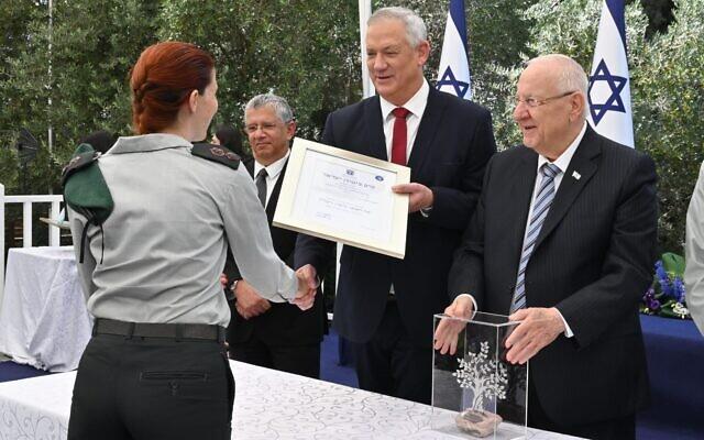 Le ministre de la Défense Benny Gantz remet le prix de la sécurité Golomb à une responsable non-identifiée des services de renseignement militaire israéliens aux côtés du président   Reuven Rivlin, à droite, et du directeur-général du ministère de la Défense,   Amir Eshel, à la résidence du président de Jérusalem, le 5 juillet 2021. (Crédit : Ariel Hermoni/Ministère de la Défense)