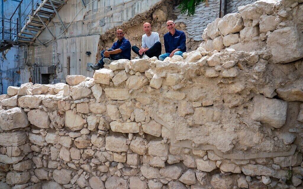 Les directeurs des fouilles assis sur la section exposée du mur de protection de l'époque du Premier Temple dans le périmètre oriental de Jérusalem. (Crédit : Yaniv Berman/ Autorité israélienne des antiquités)
