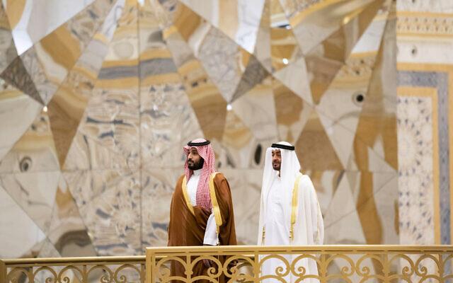 Le prince héritier saoudien Mohammed ben Salmane, à gauche, assiste à une cérémonie avec le prince héritier d'Abou Dhabi, Mohammed ben Zayed Al Nahyan, à Qasr Al Watan à Abu Dhabi, aux Émirats arabes unis, sur cette photo publiée par le ministère des Affaires présidentielles le 27 novembre 2019. (Crédit : Mohamed Al Hammadi/Ministère des Affaires Présidentielles via AP)