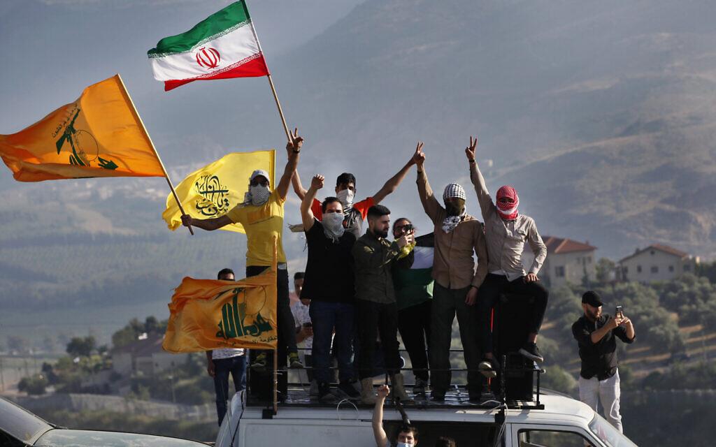 Des partisans du Hezbollah brandissent les drapeaux Palestinien, Iranien et du groupe terroriste libanais lors d'une manifestation à la frontière dans le cadre de la campagne militaire menée par les Israéliens à Gaza, à la frontière entre Israël et le Liban, devant l'implantation de Metula, en arrière-plan, le 14 mai 2021. (Crédit : AP Photo/Mohammed Zaatari)