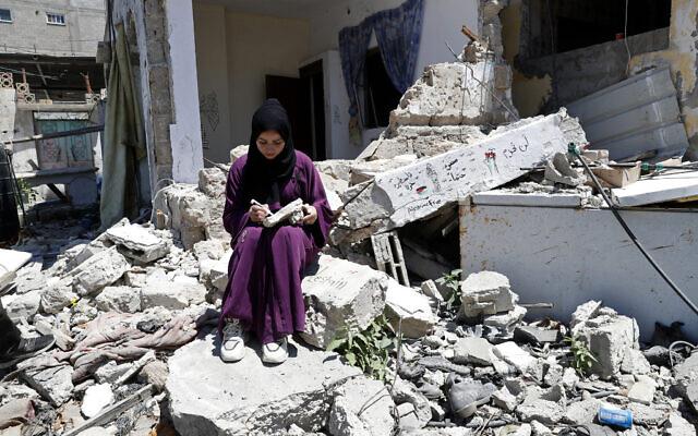 Une femme devant la maison de sa famille dans le camp de réfugiés de Rafah, dans le sud de la bande de Gaza, le 15 juin 2021. (Crédit : Adel Hana/AP)