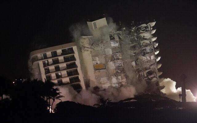 La structure restante endommagée de l'immeuble à condos Champlain Towers South s'effondre lors d'une démolition contrôlée, le 4 juillet 2021, à Surfside, Fla. (Crédit : AP/Lynne Sladky)