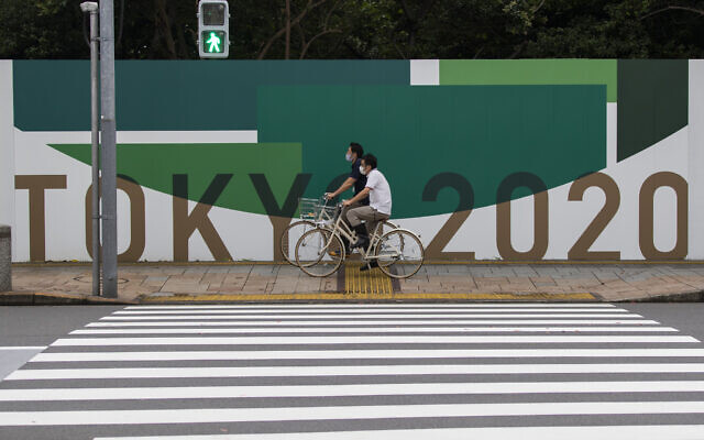 Des hommes font du vélo le long du mur installé pour fermer un parc en préparation pour les Jeux olympiques et paralympiques à Tokyo, le 1er juillet 2021. (Crédit : AP Photo/Hiro Komae)
