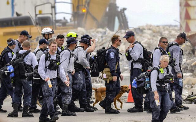 Des membres d'une équipe de recherche et de sauvetage partent après avoir travaillé sur le s ruines de l'immeuble Champlain Towers South, le 7 juillet 2021. (Crédit : Al Diaz/Miami Herald via AP)
