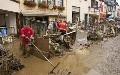 Des habitants et des commerçants tentent de dégager la boue de leurs maisons et de déplacer les meubles inutilisables à l'extérieur à Ahrweiler, dans l'ouest de l'Allemagne, samedi 17 juillet 2021. De fortes pluies ont provoqué des coulées de boue et des inondations dans l'ouest de l'Allemagne. (Crédit : Thomas Frey/dpa via AP)