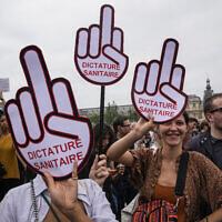 Des manifestants anti-vaccins tiennent une pancarte lors d'un rassemblement à Paris, le samedi 17 juillet 2021. (Crédit :  AP/Michel Euler)