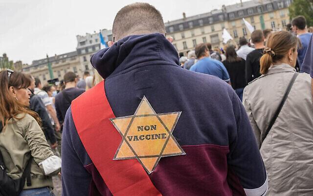 Une étoile jaune portée par un militant anti-vaccins lors d'un rassemblement à Paris, le 17 juillet 2021. (Crédit : AP Photo/Michel Euler, File)