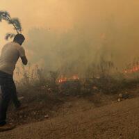 Un homme tente d'éteindre un feu de forêt, dans le village de Qobayat, dans la province du nord du Akkar, au Liban, le 29 juillet 2021. (Crédit : Hussein Malla/AP)