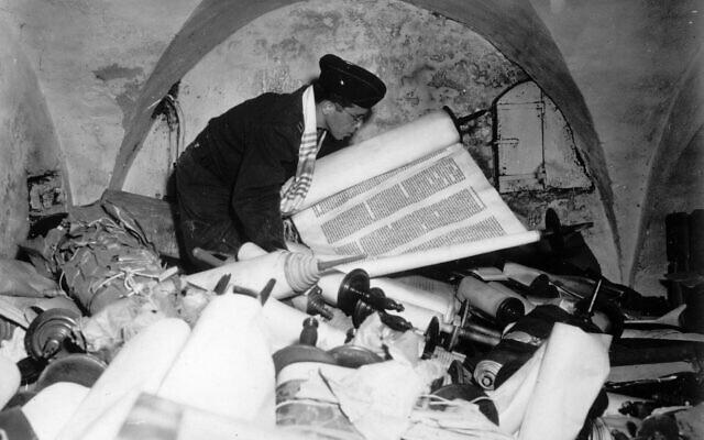 Illustration : Après la capitulation de l'Allemagne nazie, l'aumônier Samuel Blinder dans la cave de l'ancien Institut des sciences raciales à Francfort, le 6 juillet 1945. Debout, au milieu d'une collection de manuscrits et de livres provenant de tous les pays d'Europe occupés par les nazis, il examine l'un des centaines de rouleaux de la Torah. (Crédit : AP)