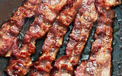 Image illustrative de bacon en train de cuire dans une poêle à frire (Crédit : Krasyuk ; iStock by Getty Images)