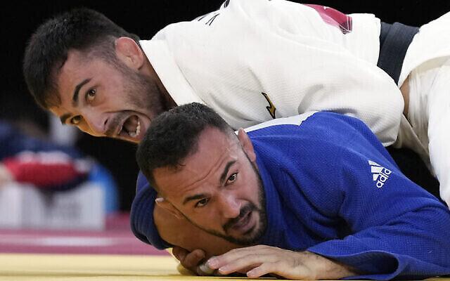 Vazha Margvelashvili de Géorgie, en haut, et Baruch Shmailov d'Israël s'affrontent pendant leur match de judo masculin de -66kg en quart de finale des Jeux olympiques d'été de 2020, le 25 juillet 2021, à Tokyo, au Japon. (Crédit : AP Photo/Vincent Thian)