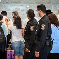Des policiers font respecter le règlement COVID-19 à l'aéroport international Ben Gurion, le 19 juillet 2021. (Crédit : AvshalomSassoni/Flash90)