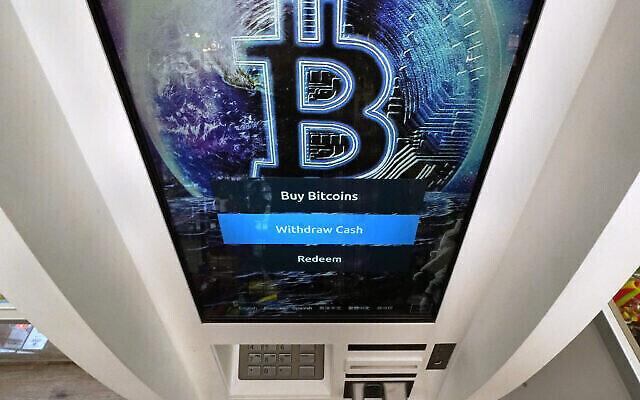 Sur cette photo d'archive du 9 février 2021, le logo Bitcoin apparaît sur l'écran d'affichage d'un distributeur de crypto-monnaies au magasin Smoker's Choice de Salem, N.H. (Crédit : AP/Charles Krupa).