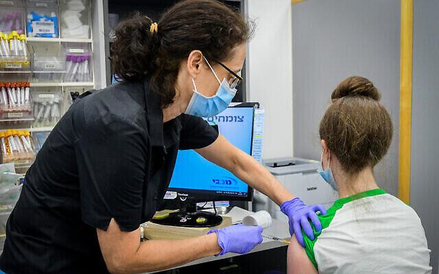 Un adolescent israélien reçoit un vaccin COVID-19 dans une clinique Maccabi à Tel Aviv, le 22 juin2021 (Crédit : Avshalom Sassoni/Flash90)
