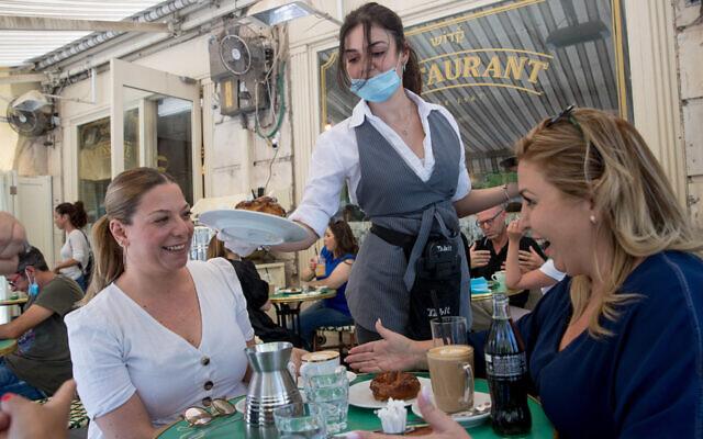 Des clients assis au Café Kadosh à Jérusalem, en mai 2020. Ce restaurant est l'un des centaines d'établissements en Israël qui ont opté pour la certification casher en dehors des auspices du Grand Rabbinat israélien. (Crédit : Yonatan Sindel/Flash90)