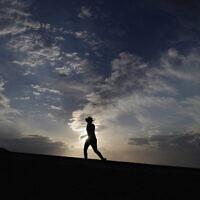 Des personnes marchent le long d'un sentier, le 11 juillet 2021, dans le parc national de la Vallée de la Mort, en Californie (Crédit : AP/JohnLocher).