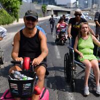 Des activistes handicapés bloquent l'autoroute Ayalon à Tel Aviv le 25 juillet 2021. (Crédit : Tomer Neuberg/Flash90)