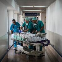 Illustration : Des médecins et des infirmières traitent un patient à l'hôpital Wolfson à Holon. (Crédit : Hadas Parush/Flash90)