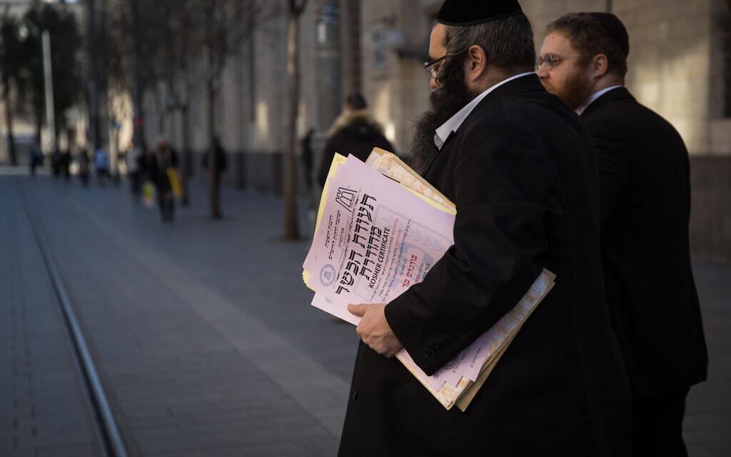 Des représentants ultra-orthodoxes du Grand Rabbinat traversent la rue Jaffa à Jérusalem alors qu'ils remettent un certificat de cacherout à un restaurant local, le 31 décembre 2019. (Crédit : Hadas Parush/Flash90)