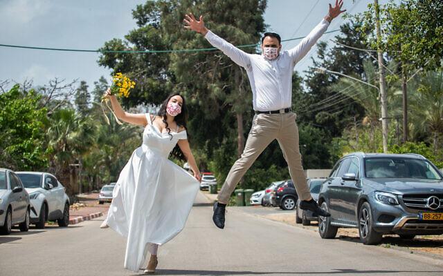 Photo d'illustration : Gal Sade Knigsfild et Nofar Almakias posent en portant le masque avant leur mariage au Moshav Yashresh, le 6 avril 2020. (Crédit : Yossi Aloni/Flash90)