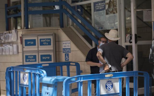 Un homme fait la queue à l'entrée d'une agence de l'Institut national d'assurance dans le centre-ville de Jérusalem, le 21 septembre 2020. (Crédit : Nati Shohat/Flash90)