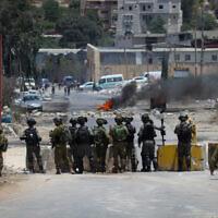 Des manifestants palestiniens jettent des pierres aux soldats israéliens pendant des affrontements lors d'une manifestation à Beita, en Cisjordanie, le 8 juin 2021. (Crédit :  Nasser Ishtayeh/Flash90