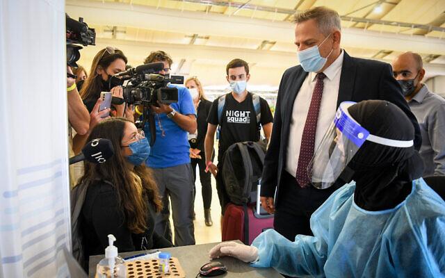 Le ministre de la Santé Nitzan Horowitz  supervise des techniciens médicaux qui testent les passagers pour le COVID-19 à l'aéroport international Ben Gurion près de Tel Aviv, le 12 juillet 2021. (Crédit : Flash90)