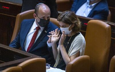 Le Premier ministre Naftali Bennett, à gauche, parle avec la ministre de la Protection de l'environnement Tamar Zandberg dans le plénum de la Knesset, le 12 juillet 2021. (Crédit : Olivier Fitoussi/Flash90)