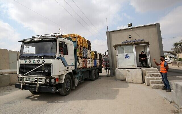 Un policier palestinien fait signe à un camion alors qu'il entre par le passage de Kerem Shalom dans la bande de Gaza, le 1erseptembre 2020, après un accord avec Israël sous médiation qatarie. (Crédit : SAIDKHATIB / AFP)