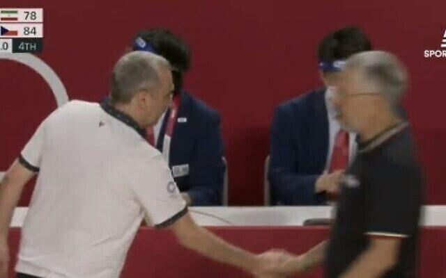 Ronen Ginzburg, l'entraîneur israélien de l'équipe nationale tchèque de basket-ball masculin, serre la main de son homologue iranien, Mehran Shahintab, aux Jeux olympiques le 25 juillet 2021 (Crédit : capture d'écran : Sports 5)