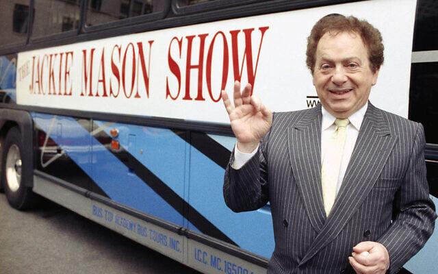 L'acteur et comédien Jackie Mason en 1992, à côté d'un autobus affichant un panneau publicitaire pour son émission de télévision. (Crédit : photo AP)