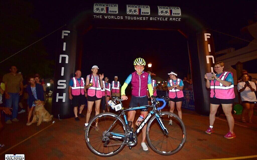 Leah Goldstein sur la ligne d'arrivée de la Race Across America 2021. Elle est la première femme à remporter le classement général en solo en 39 ans d'histoire de la RAAM, terminant le parcours en 11 jours, 3 heures et 30 minutes (Crédit : Vic Armijo/RAAM Media)