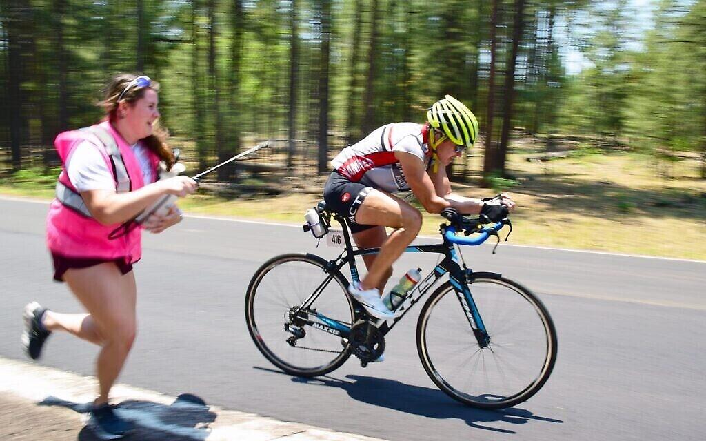 L'un des membres de l'équipe de Leah Goldstein luijtte de l'eau alors qu'elle se hisse à la 2e place du classement général à travers Tuba City, Arizona dans Race Across America 2021, le 18 juin 2021 (Crédit : Vic Armijo/RAAM Media)