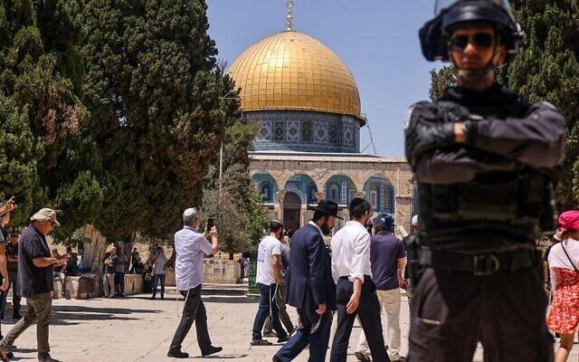 Un membre des forces de sécurité israéliennes monte la garde alors qu'un groupe de Juifs entre sur le Mont du Temple à Jérusalem, lors de la journée de jeûne annuel de Tisha B'Av, le 18 juillet 2021. (Crédit : Ahmad Gharabli/AFP)