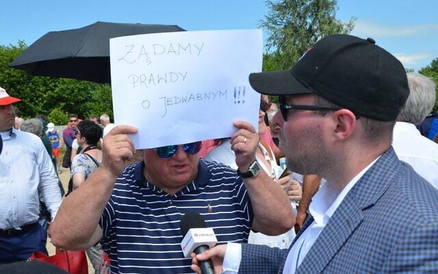 """Un nationaliste polonais brandit un panneau où est écrit """"Nous demandons   la vérité sur  Jedwabne,"""" sur le site d'un pogrom commis pendant la Shoah à Jedwabne, en Pologne, le 10 juillet 2021. (Crédit : Krzysztof Bielawski)"""