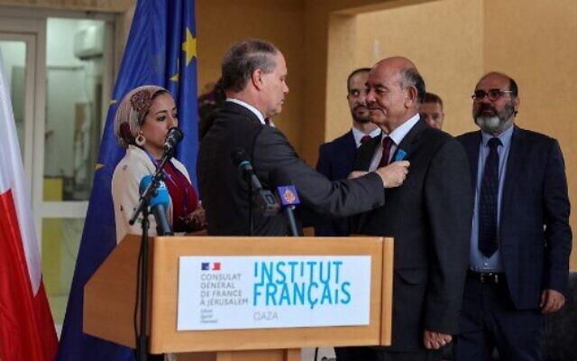 Le consul général français à Jérusalem  Rene Troccaz décore l'avocat palestinien des droits de l'Homme Raji Sourani de l'ordre national du mérite à l'institut français de Gaza, le 7 juillet 2021. (Crédit :  MOHAMMED ABED / AFP)