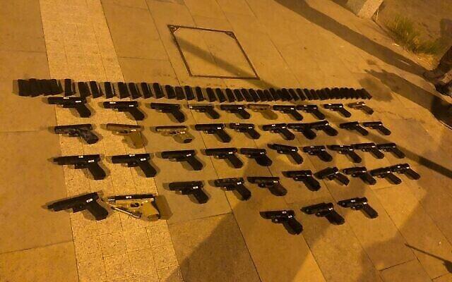 Des dizaines d'armes à feu saisies lors d'une opération de contrebande en provenance du Liban, le 10 juillet 2021. (Crédit : Forces de défense israéliennes)