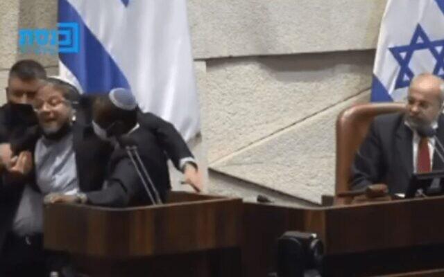 """Le député du sionisme religieux Itamar Ben Gvir (G) a été retiré de force du podium de la Knesset et éjecté de la séance plénière après avoir traité le député de la Liste commune Ahmed Tibi (D) de """"terroriste"""", le 26 juillet 2021. (Capture d'écran : Knesset Channel)"""
