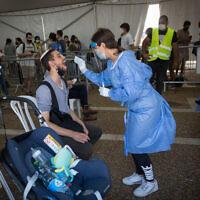 Un technicien prélève des échantillons par écouvillonnage pour le COVID-19 dans un centre de tests géré par la municipalité de Tel Aviv sur la place Rabin à Tel Aviv, le 20 juillet 2021. (Crédit : Miriam Alster/ Flash90)