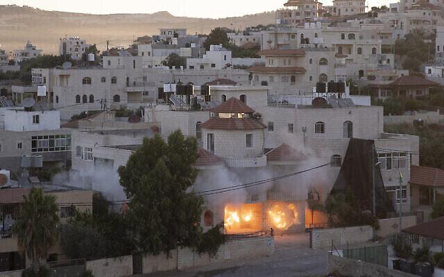 Une unité de l'armée israélienne démolit la maison de l'Américain palestinien Muntasser Shalaby à l'aide d'explosions contrôlées dans le village cisjordanien de Turmus Ayya, au nord de Ramallah, jeudi 8juillet 2021. Shalaby est accusé d'être impliqué dans une attaque meurtrière contre des Israéliens en Cisjordanie en mai. (Crédit : AP Photo/Nasser Nasser)