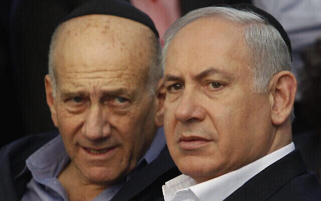 Le premier ministre de l'époque, Benjamin Netanyahu, à droite, et l'ancien premier ministre Ehud Olmert, à gauche, assistent aux funérailles du MK du Likoud, Zeev Boim, à Binyamina, le 21 mars 2011. (AP Photo/Moti Milrod, Pool)