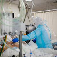 Le personnel du centre médical Shaare Zedek portant des vêtements de protection déplace des patients vers la nouvelle salle de coronavirus de l'hôpital à Jérusalem, le 7 janvier 2021. (Olivier Fitoussi/Flash90)