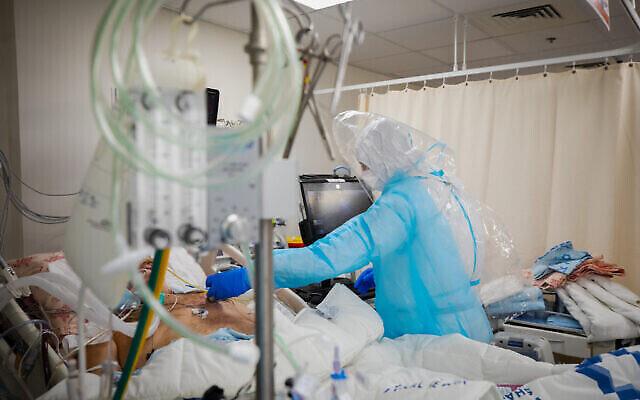 Le personnel du centre médical Shaare Zedek portant des vêtements de protection déplace des patients vers la nouvelle salle de coronavirus de l'hôpital à Jérusalem, le 7 janvier 2021. (Olivier Fitoussi / Flash90)